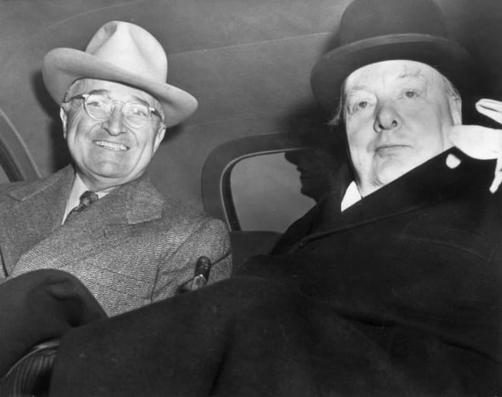 Harry Truman sits in a car next to Winston Churchill