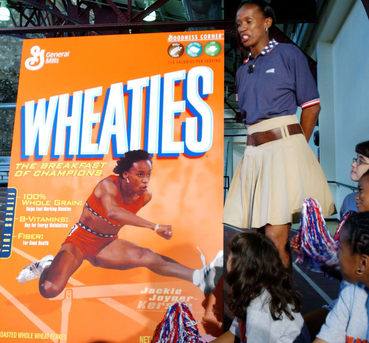 Former Track and Field Olympian Jackie Joyner-Kersey stands with a poster of her new Wheaties box after it was unveiled in 2004.