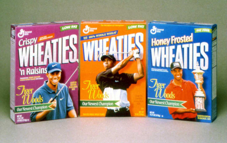 Three different Wheaties boxes featuring Tiger Woods sitting together on a table