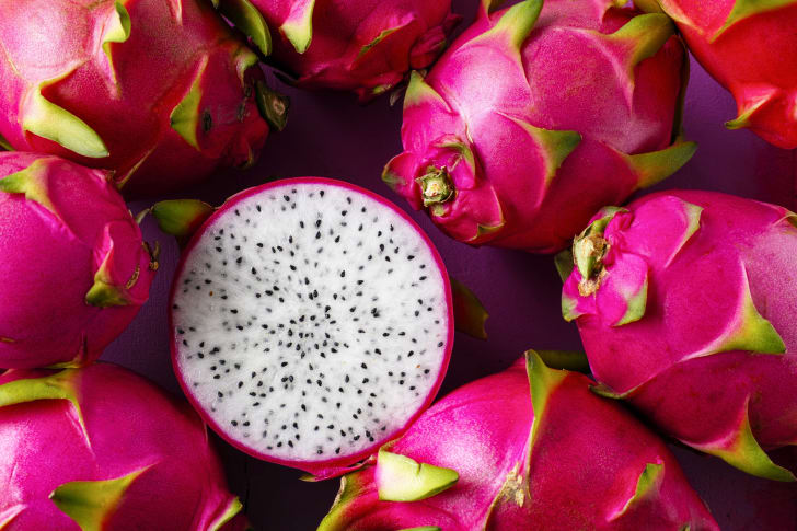 Whole hot pink dragon fruits surrounding a dragon fruit cut in half to reveal the black-speckled white inside.