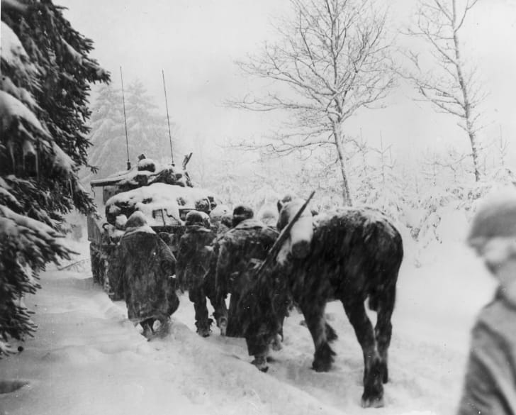 Members of the American 82nd Airborne Division trudging through the snow behind a tank during the Battle of the Bulge