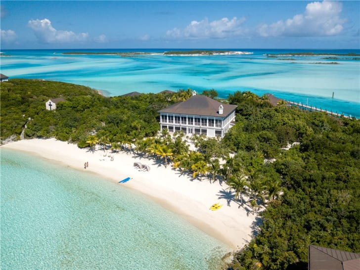 An aerial view of a mansion on the beach on a private island