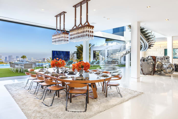 A bright white dining room with floor-to-ceiling windows looking out upon Los Angeles