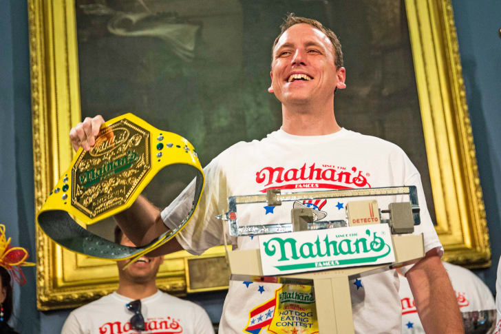 Image of Joey Chestnut standing on a scale and holding the prize-winning mustard yellow bet for winning the hot dog eating competition