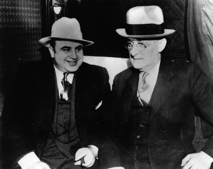 Vintage photograph of Al Capone standing next to some other unknown nameless guy in a fedora. Or maybe a bowler hat.