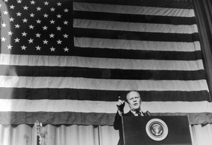 Gerald Ford stands in front of an American flag while delivering a speech