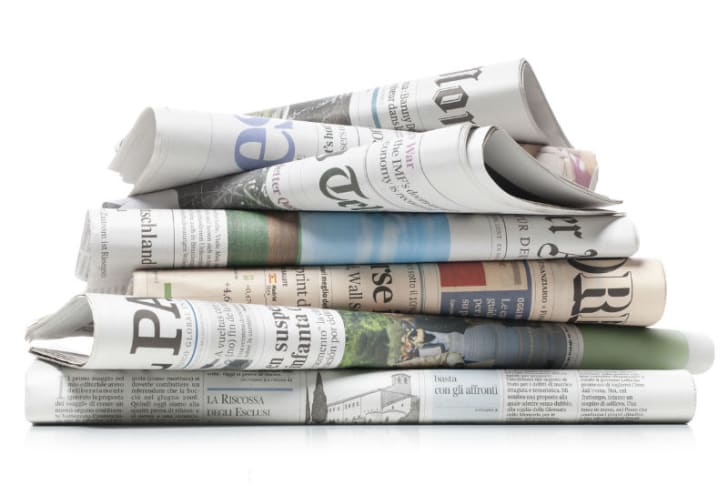 Newspapers are stacked in a pile