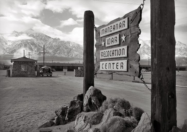 Wooden sign at entrance to the Manzanar War Relocation Center with a car at the gatehouse in the background
