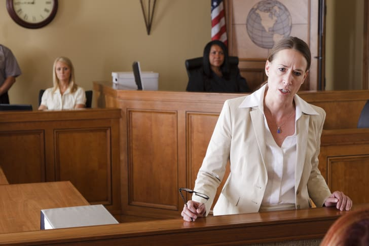 A serious-looking lawyer standing up and arguing her case in court