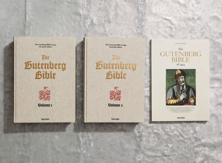 The two volumes of Taschen's Gutenberg Bible and its companion text sitting on a table