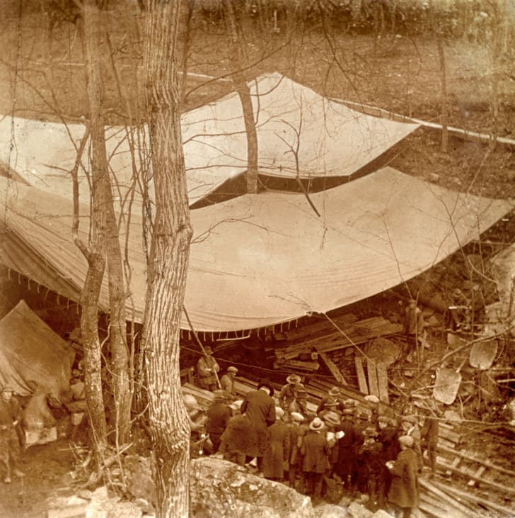 Men digging a shaft—which is covered by a tarp—to Collins.