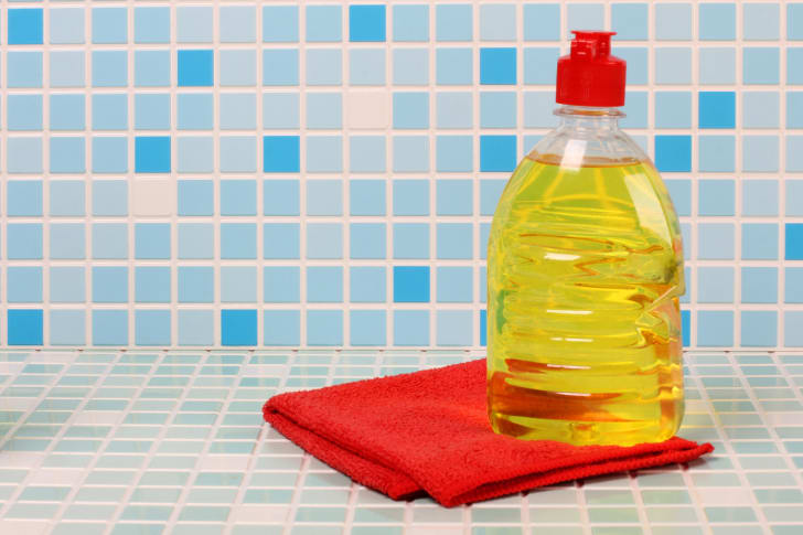 A bottle of dish soap against a tiled background