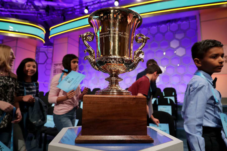 Competitors walk past the championship trophy on display during the third round of the 91st Scripps National Spelling Bee at the Gaylord National Resort and Convention Center May 30, 2018