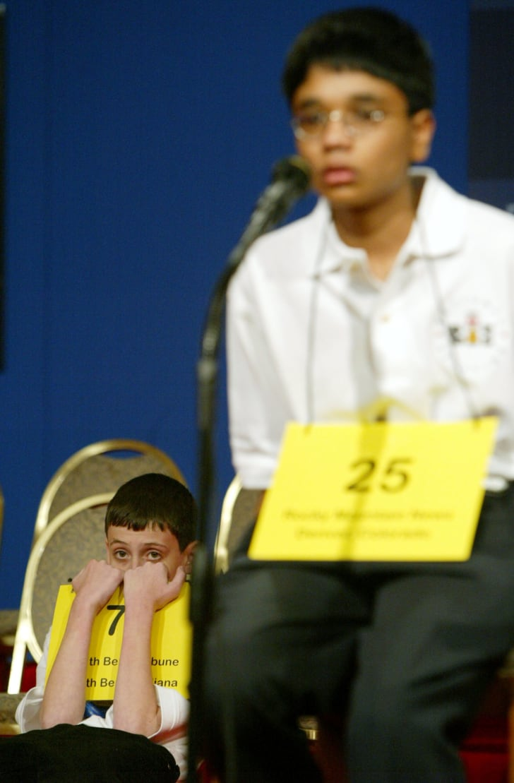 David Tidmarsh peers over his placard as his final opponent, Akshay Buddiga, spells a word during the National Spelling Bee June 3, 2004