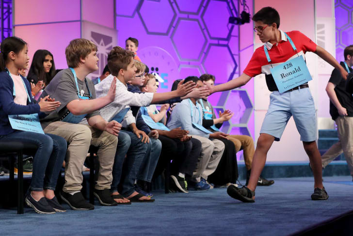 Despite misspelling his word, Ronald Walters of Onalaska, Wisconsin, is high-fived by his fellow competitors during the third round of the 91st Scripps National Spelling Bee at the Gaylord National Resort and Convention Center May 30, 2018