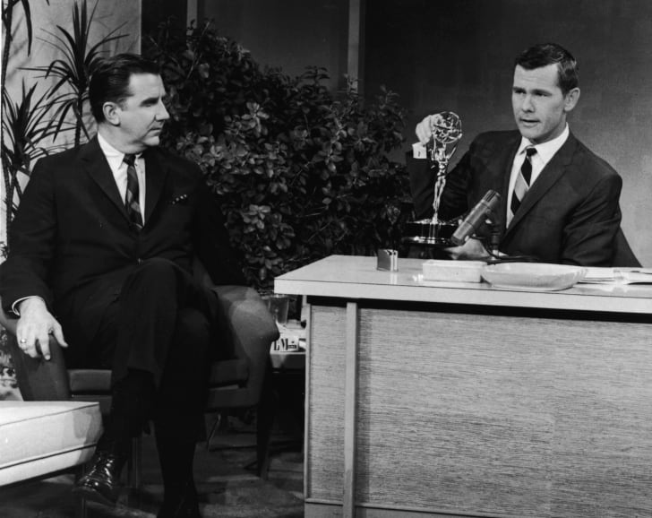Host Johnny Carson sits with an Emmy award on his desk, as announcer Ed McMahon looks on, in a still from 'The Tonight Show With Johnny Carson,' 1963