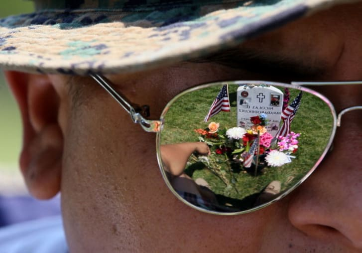 Ricky Parada sits at the grave of his little brother Cpl. Nicolas D. Paradarodriguez who was killed in Afghanistan, at Section 60 on Memorial Day at Arlington National Cemetery on May 28, 2012 in Arlington, Virginia
