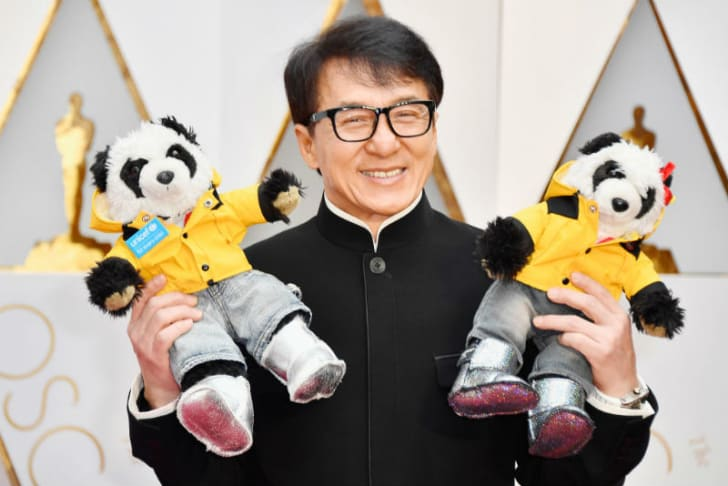 Jackie Chan poses with two stuffed pandas