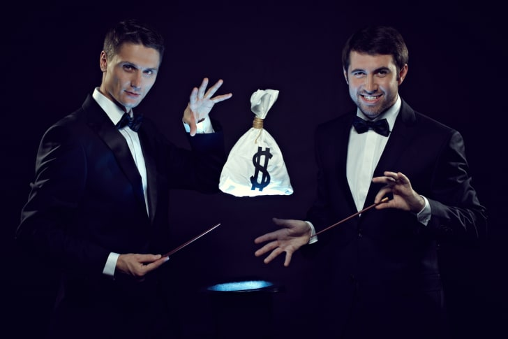Two magicians playing a trick with a bag of money