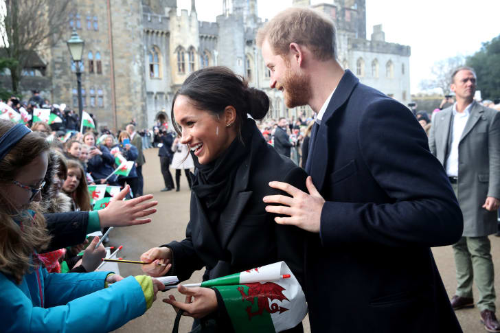 Prince Harry and his fiancee, Meghan Markle, sign autographs and shake hands with children as they arrive to a walkabout at Cardiff Castle on January 18, 2018 in Cardiff, Wales.