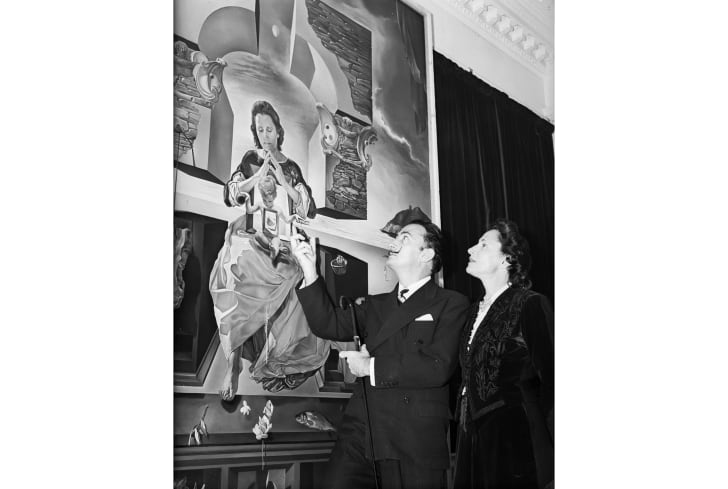 Salvador Dalí and his wife Gala look up at one of his paintings.