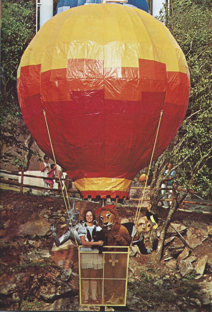Dorothy and other characters ride in a fake hot air balloon