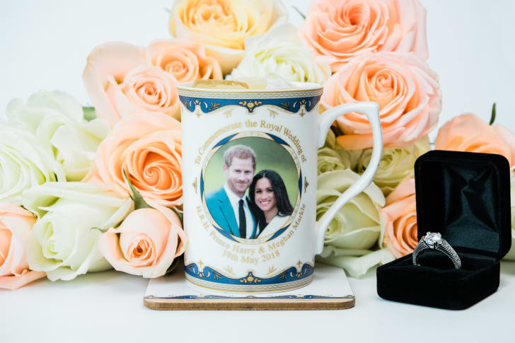 A commemorative mug with a photo of Prince Harry and Meghan Markle sits next to an engagement ring and roses.