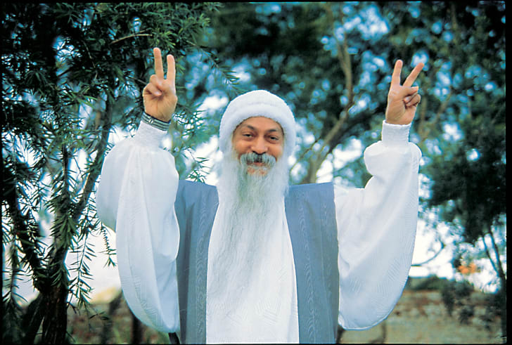 An image of Bhagwan Shree Rajneesh making the peace sign with his fingers