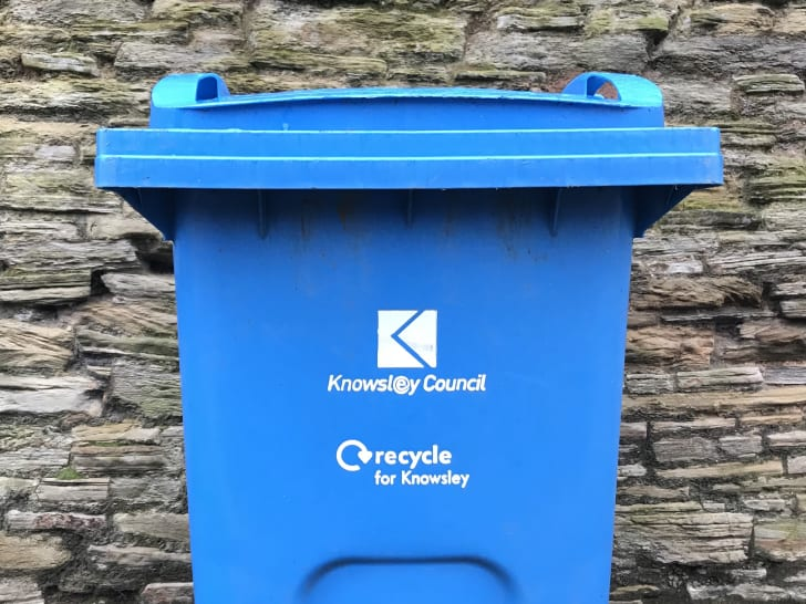 A bright blue trash can reads 'Knowsley Council: Recycle for Knowsley.'