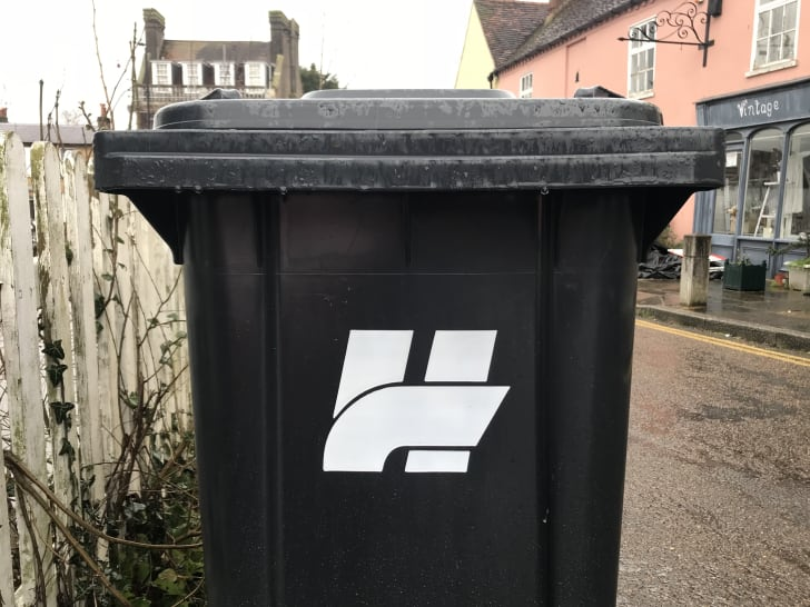 A black trash can features an 'H' logo.
