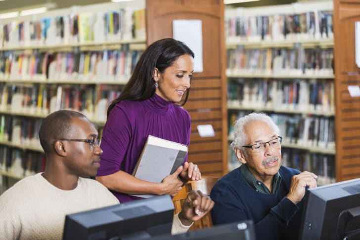 A librarian helping two patrons at computers