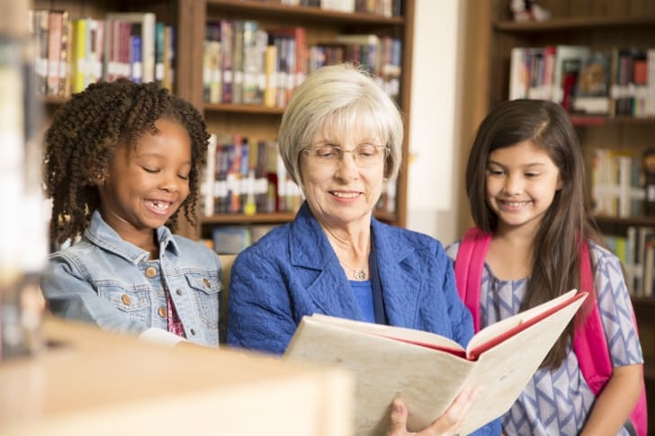 A senior librarian reading to small children