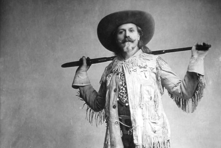 Buffalo Bill stands with his rifle on his shoulder in a studio portrait