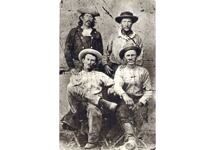 A seated tin-type portrait of four Pony Express riders