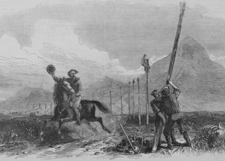 A man on a horse waves his hat at men putting up a telegraph pole.