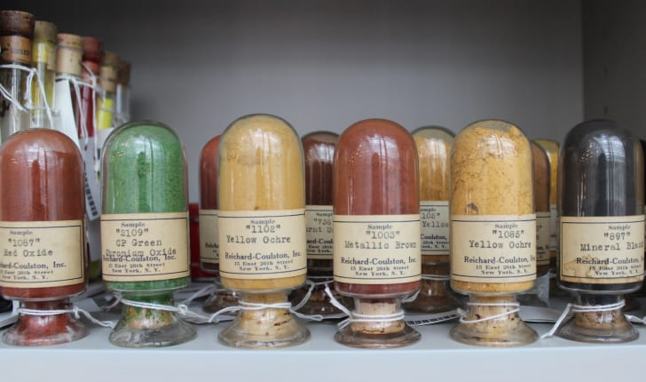 Colorful pigments in vintage glass jars sit on a shelf