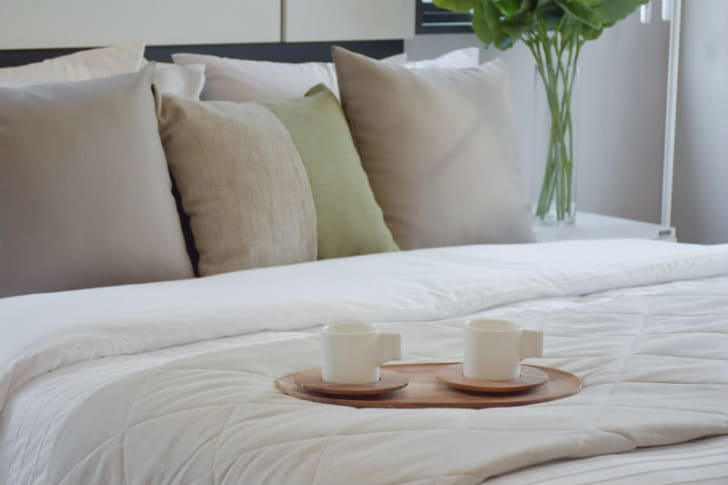 Two coffee cups sit on a hotel bed