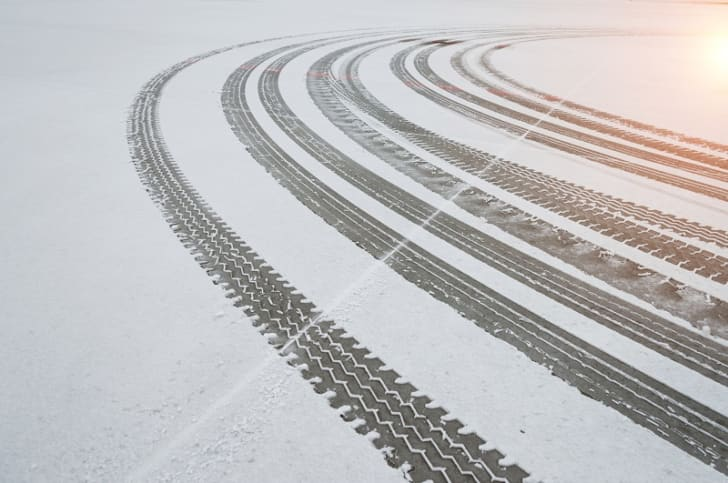 Tire tracks appear on a snow-covered road