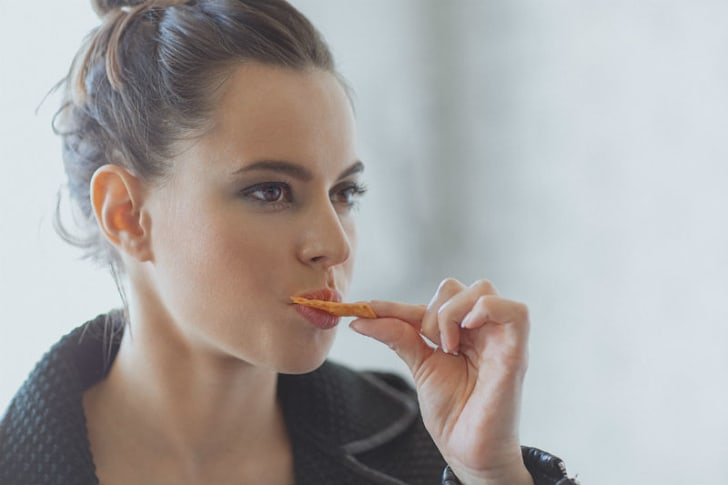 A woman snacks on a chip