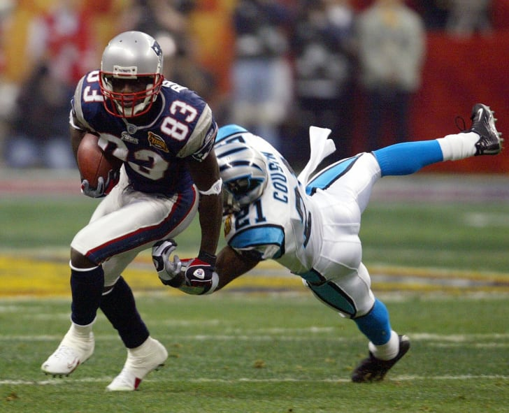 New England Patriots wide receiver Deion Branch (L) breaks away from Terry Cousins (R) of the Carolina Panthers in the first quarter of Super Bowl XXXVIII at Reliant Stadium 01 February 2004 in Houston, TX