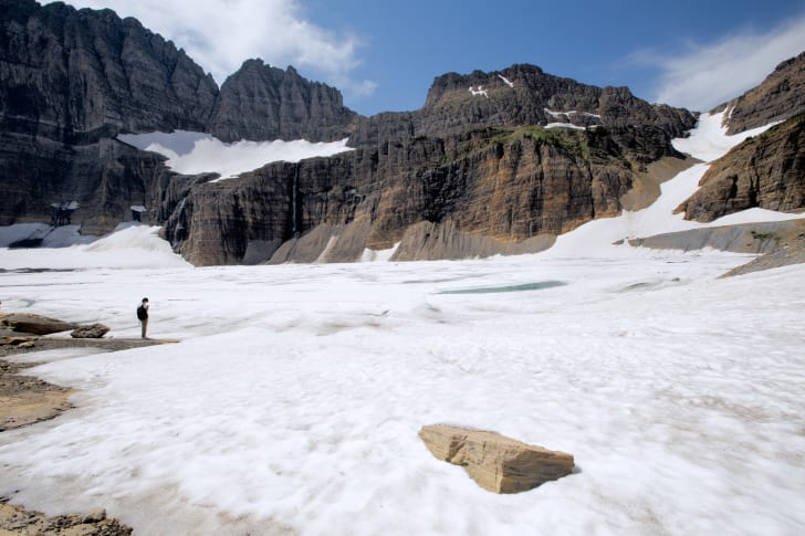 person stands by ice and snow in glacier national park