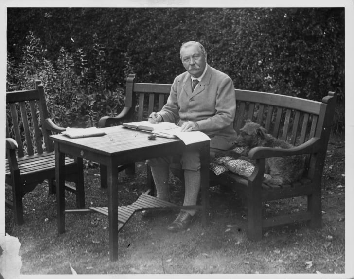 Portrait of Sir Arthur Conan Doyle sitting at a table in his garden, Bignell Wood, New Forest, 1927