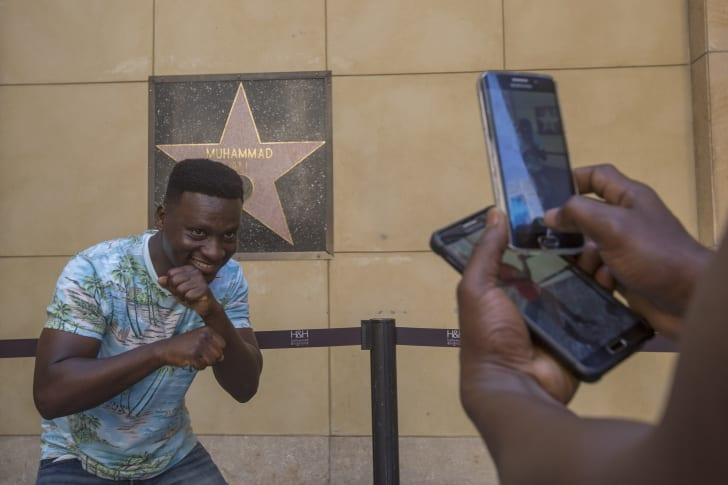 Eric Obeng, attending university in the U.S. from Ghana, poses for a friend while paying respect to the late Muhammad Ali at his star on The Hollywood Walk of Fame on June 4, 2016 in Hollywood, United States