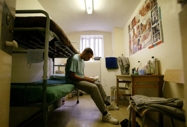 An inmate reads a book in his prison cell