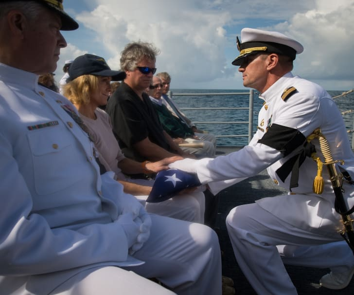 Neil Armstrong's widow being presented with the U.S. flag during the astronaut's burial at sea