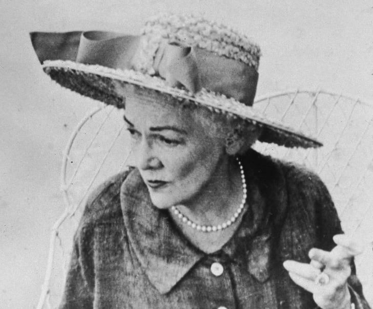 Author Katherine Anne Porter sitting in a chair wearing a hat with a bow on it.