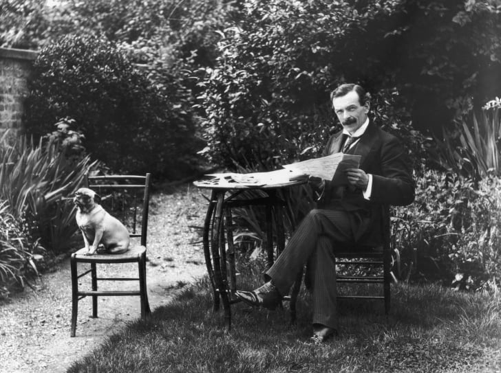 David Lloyd George sitting outside with his dog and reading a newspaper.