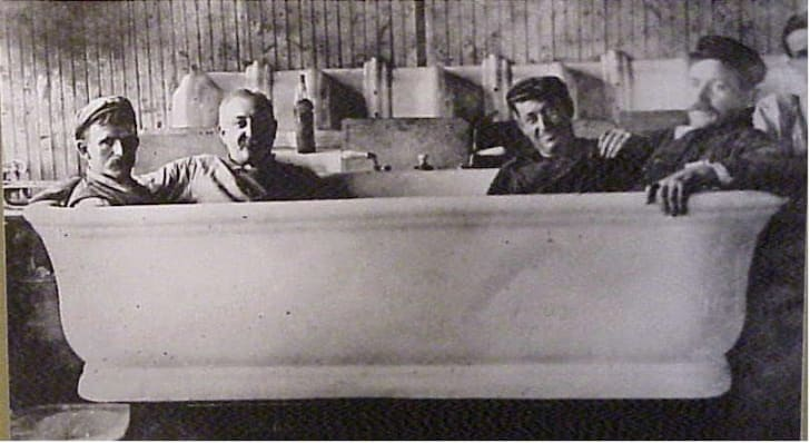Four men sit in an extra-large bathtub.