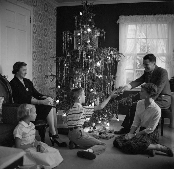 A family around a lighted Christmas tree, circa 1955.