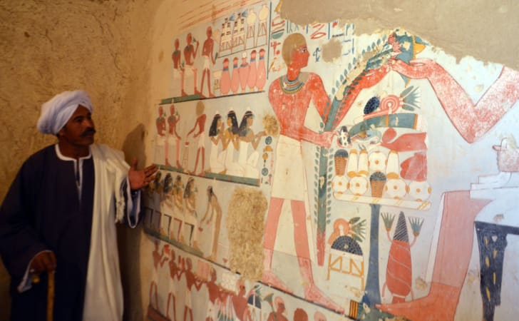 An Egyptian laborer stands next to an ancient Egyptian mural found at the newly discovered 'Kampp 161' tomb at Draa Abul Naga necropolis in Luxor, Egypt.